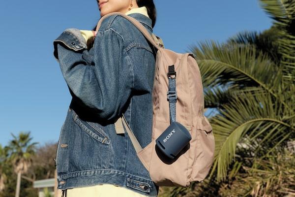 Genç bir kadının sırt çantasına asılmış XB13 EXTRA BASS(TM) Taşınabilir Kablosuz Hoparlörün görüntüsü.